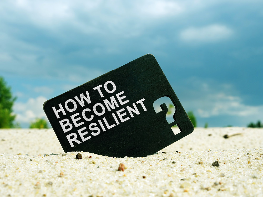 """Image: Sign in the sand that says """"How to become resilient?"""""""