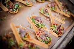 Edible parmesan spoons holding caesar salad with crumbled bacon