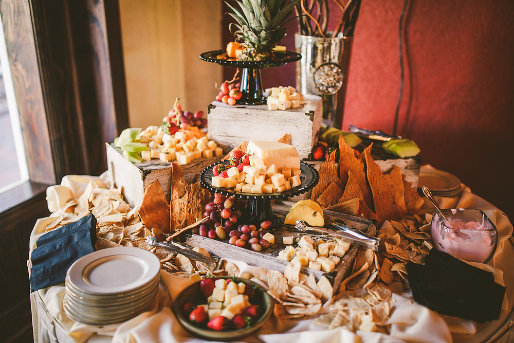 A table covered with various meats, cheeses, and fruits as a charcuterie display at an indoor wedding