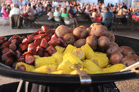 Crawfish boil party photo of a platter of sausage, potatoes, and corn on the cob with a crowd of people in the background