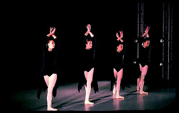 Four Mill Ballet School Trainees stand with their arms overhead