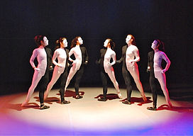 A photo of six dancers leaning in towards the middle costume half black & white