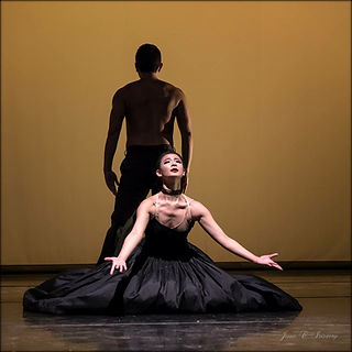 female dancer in a large skirt kneeling with open arms reaching out male dancer facing upstage