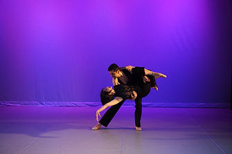 a male dancer lifting a female dancer in a dip towards the floor