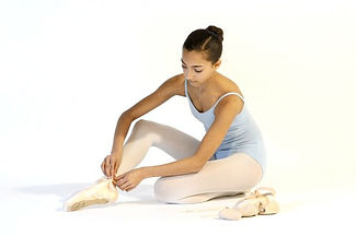 Young girl puts on pointe shoes