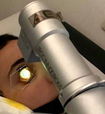 מטופל תחת מכשיר בזמן הקרנת העין באולטרא סגול בטיפול קרוס לינקינג