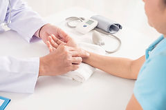 Medical Clinic doctor checking the pulse of a patient