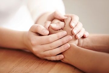 Two people, each clasping both hands over the other's from across a table.