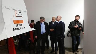 Premiér České republiky se zaujetím kouká s rukama v kapsách na letecký simulátor Zall Letov Simulátory