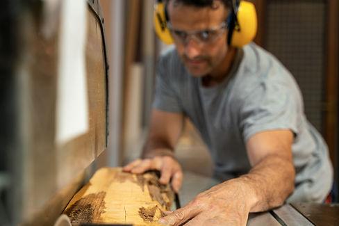 carpenter-cutting-wood-with-machine-wear