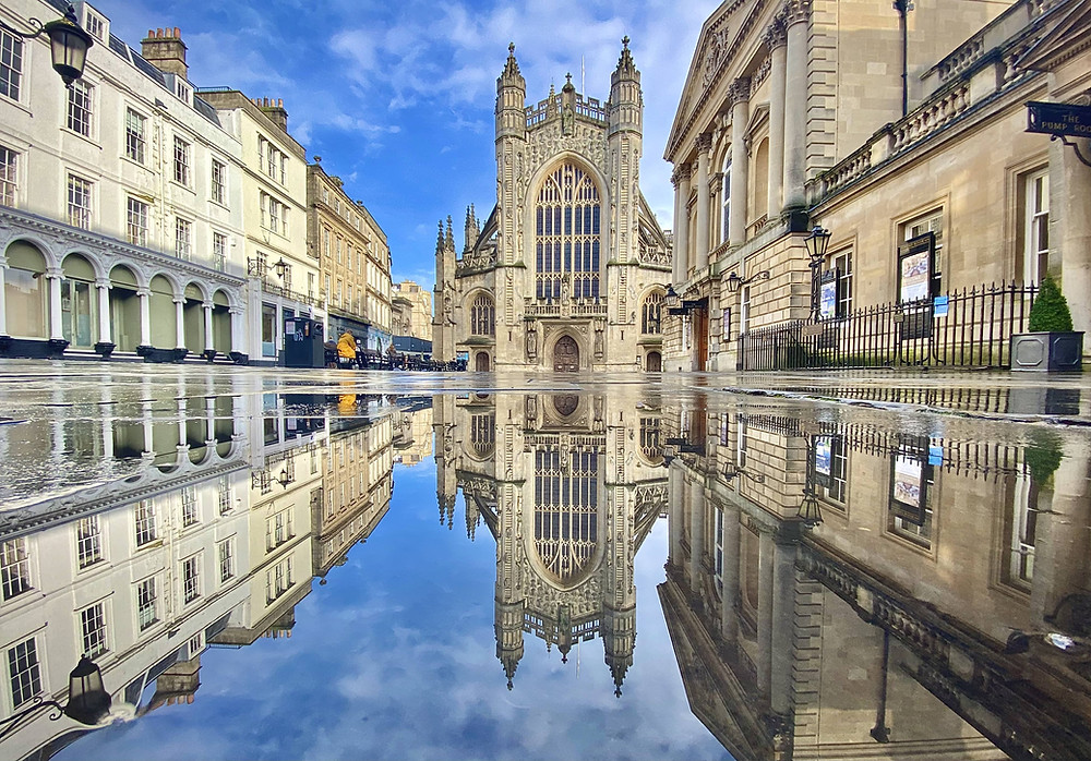A mirror-like reflection of Bath Abbey and Roman Baths