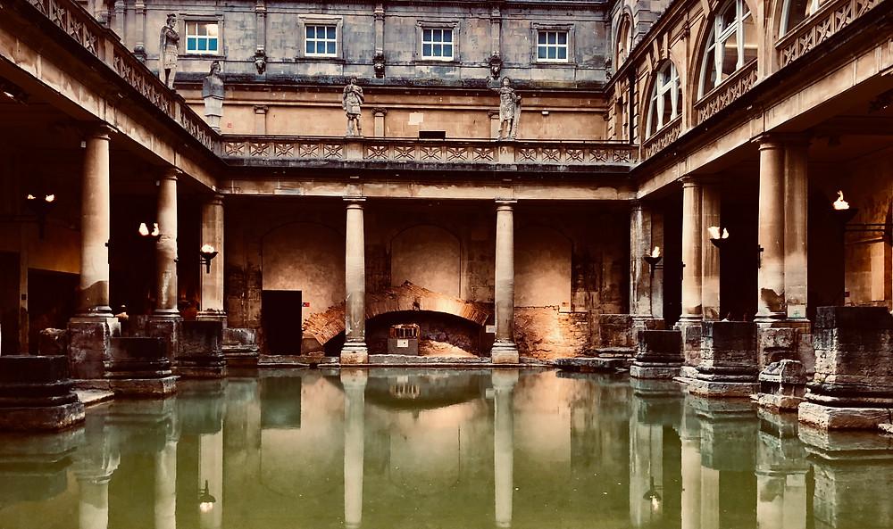 A torchlit Roman Baths as dusk approaches