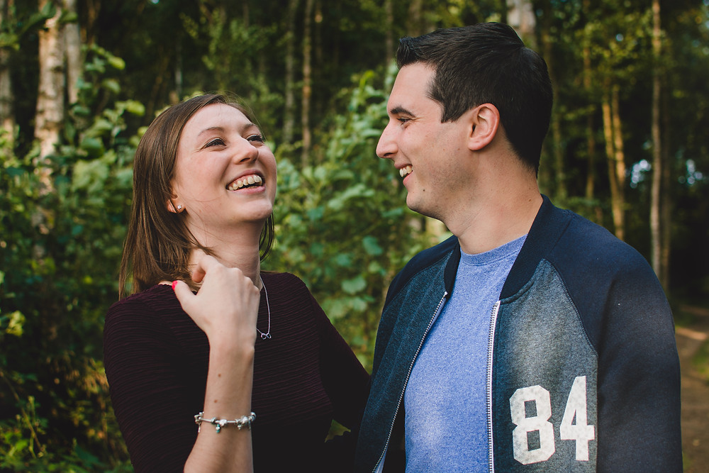 couple laughing in the forest during an engagement photoshoot