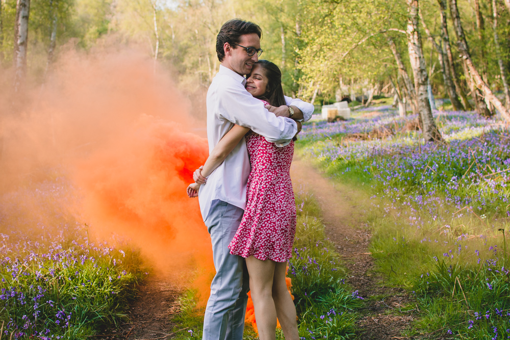 Couple have a big hug during their engagement photoshoot in Newbury with an orange smoke bomb behind them