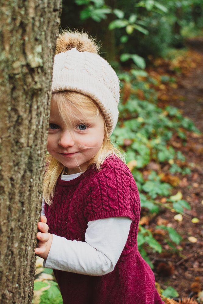 During an autumn family photoshoot, this little girl is playing hide and seek with her mummy
