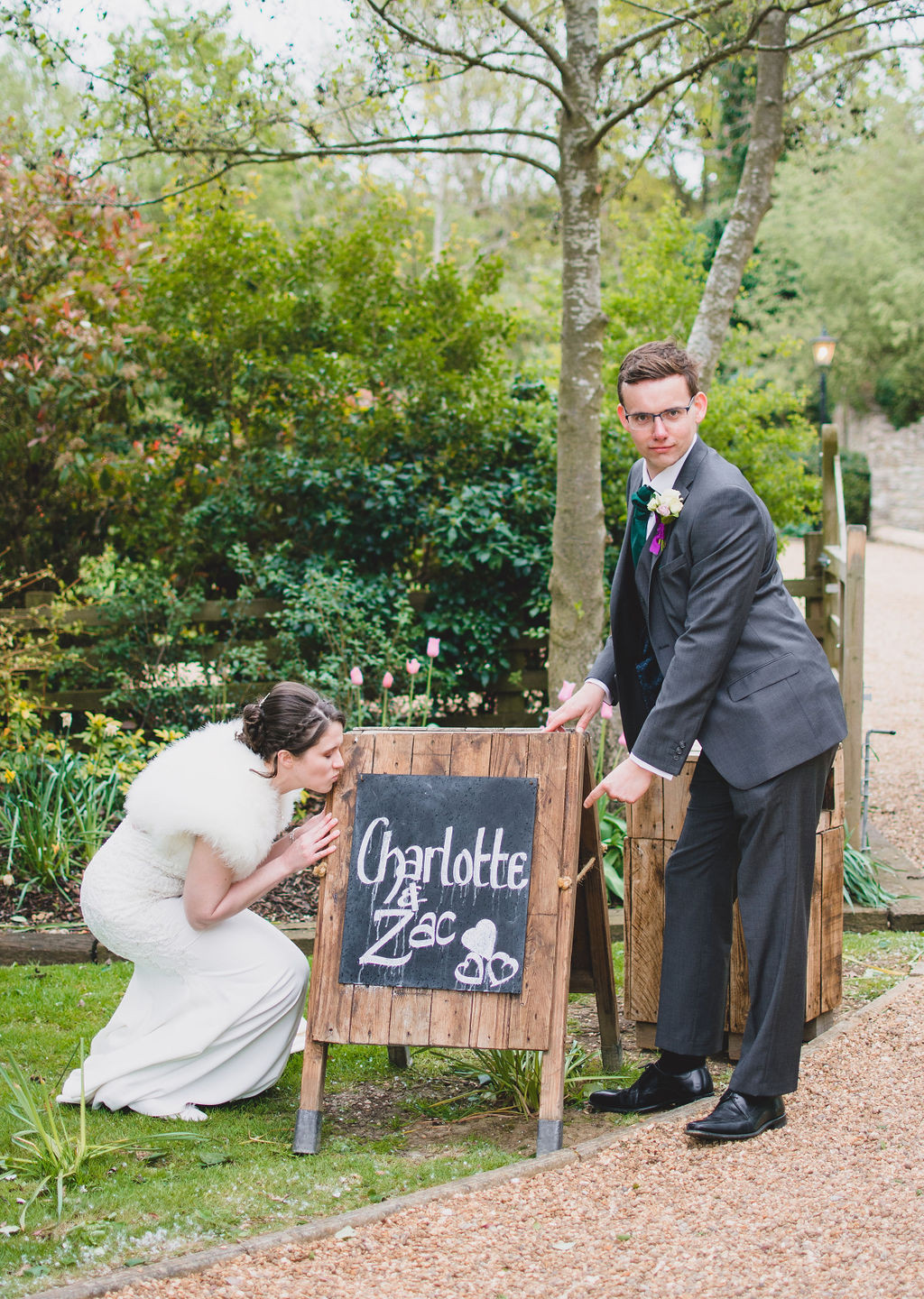 Bride and Groom posing by a handwritten sign of their names