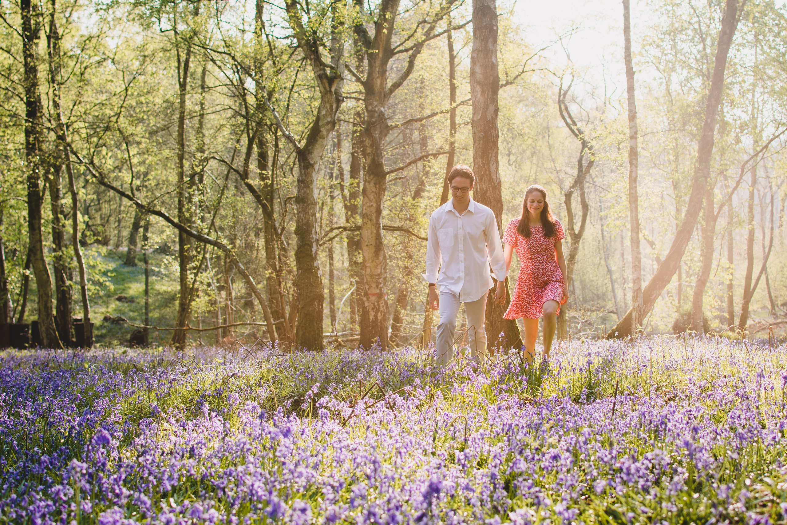 Couple are walking through a forest of bluebells during their engagement shoot in Newbury