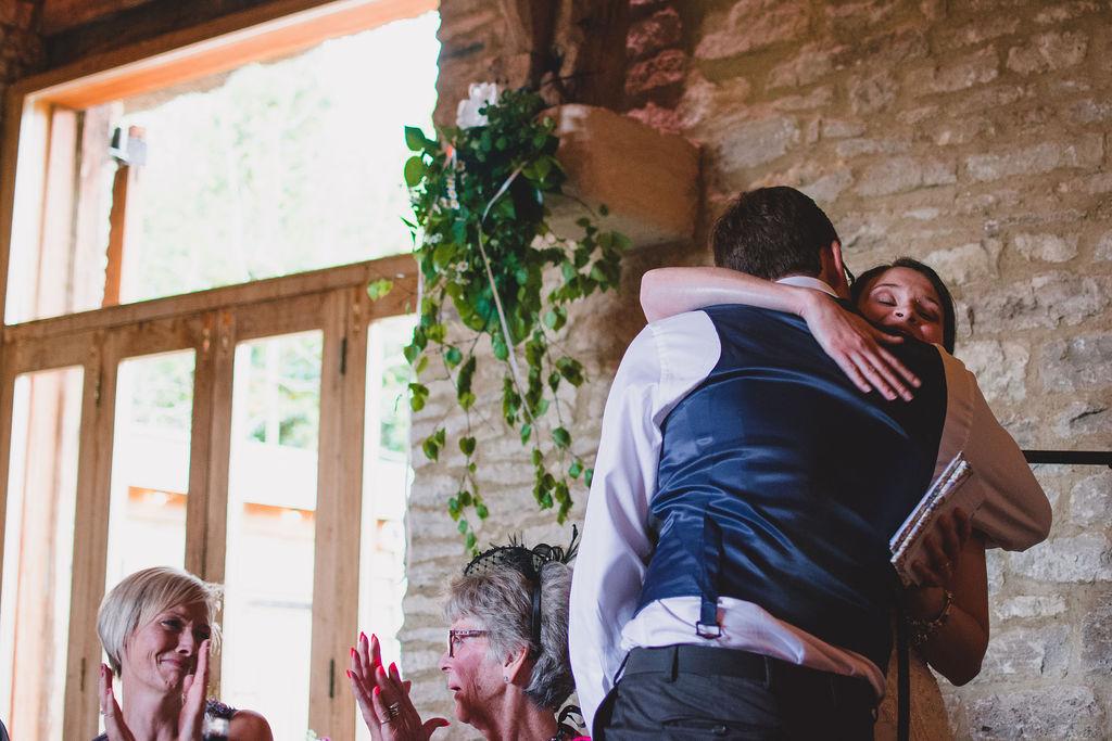 Bride and groom hug after the bride's speech