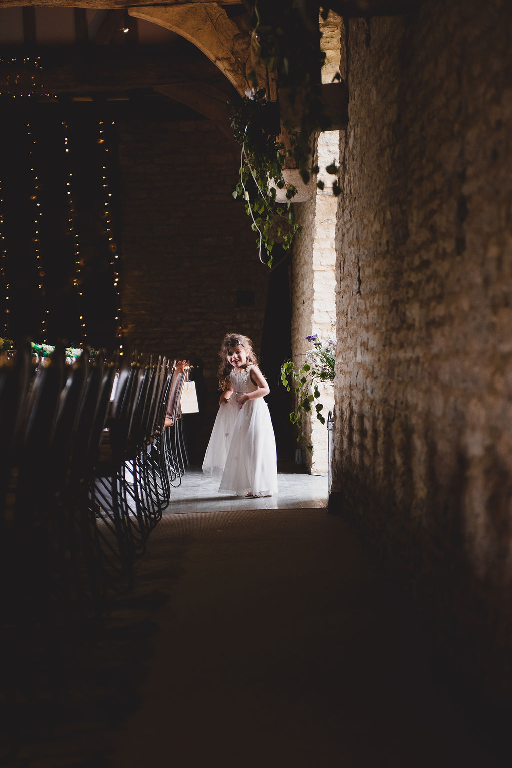 Flower girl gazing down the row of chairs at The Tythe Barn