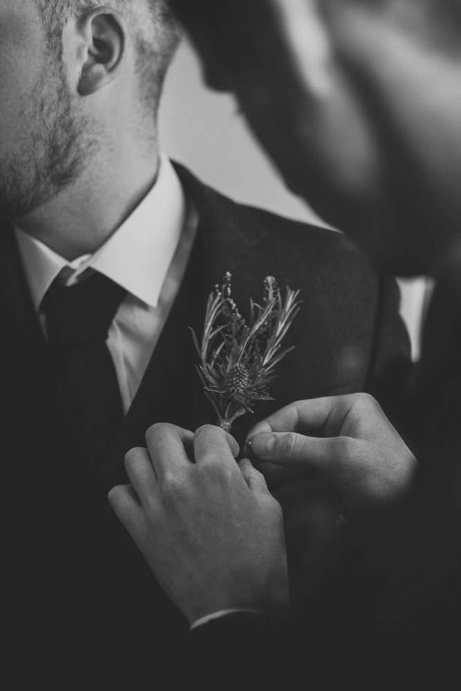 Scottish thistle buttonhole being attached on the morning of the wedding