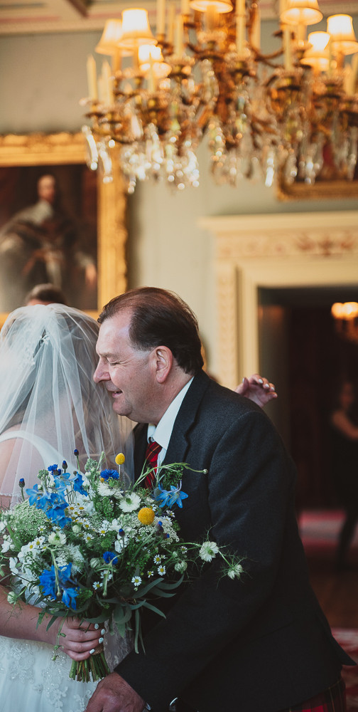 Father of the bride embraces the bride when they reach the top of the ceremony room
