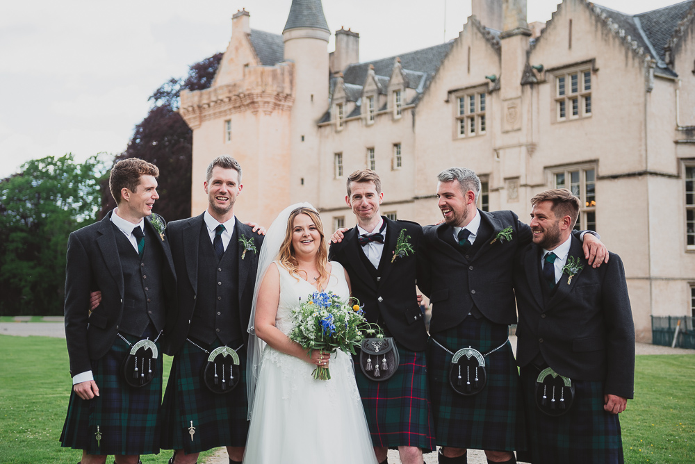 Groomsmen in kilts with the bride and groom on their wedding day