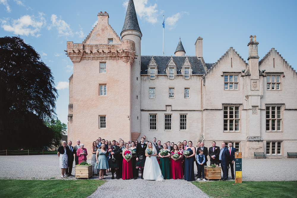 Group photograph outside the castle after the wedding ceremony.
