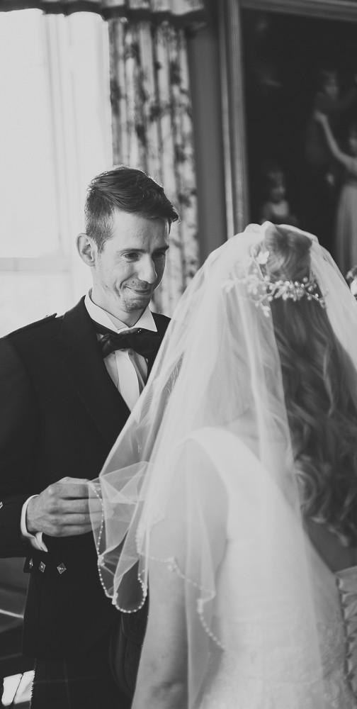 Groom moves veil from brides face