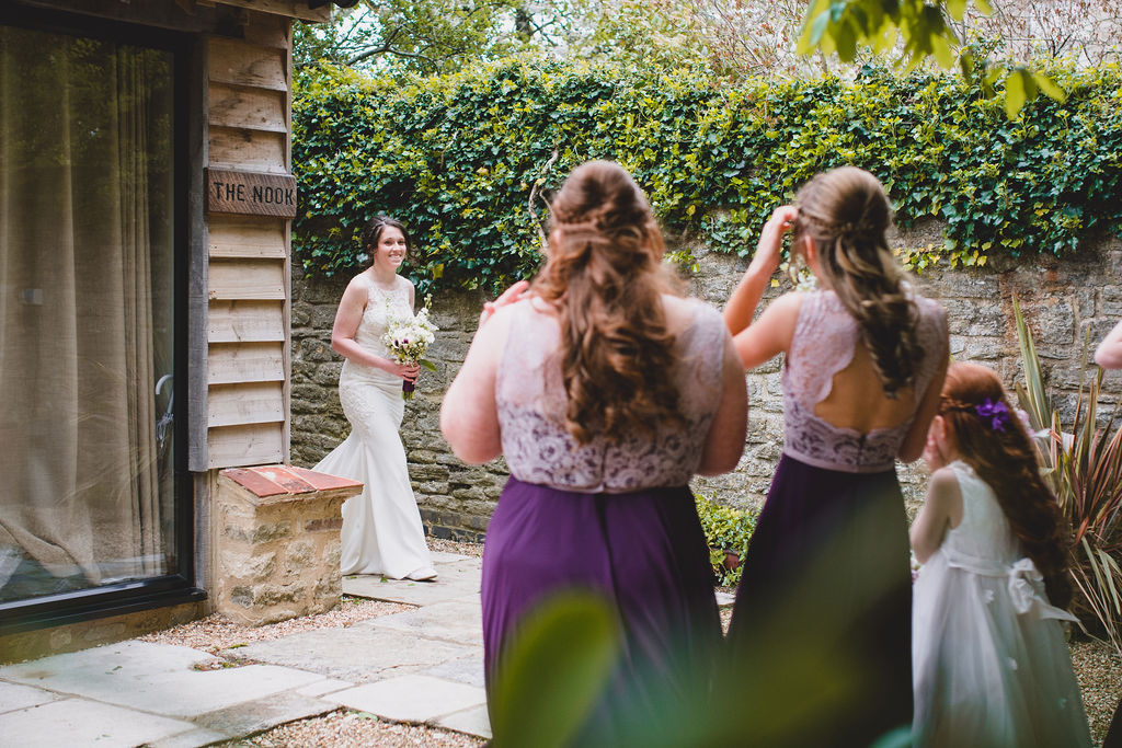 Bridesmaids see the bride in the wedding dress for the first time