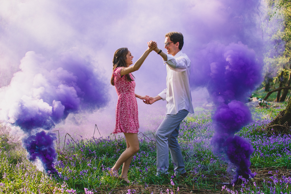 Couple are dancing around in a field of bluebells with purple smoke bombs on either side during their engagement shoot in Newbury