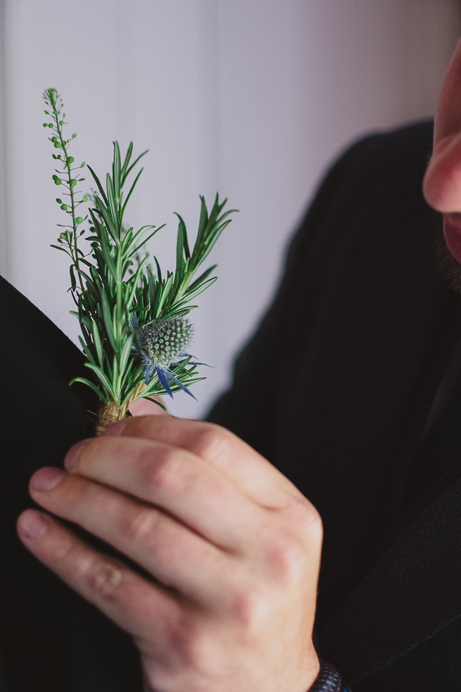 Groomsman attached the Scottish thistle buttonhole to the groom