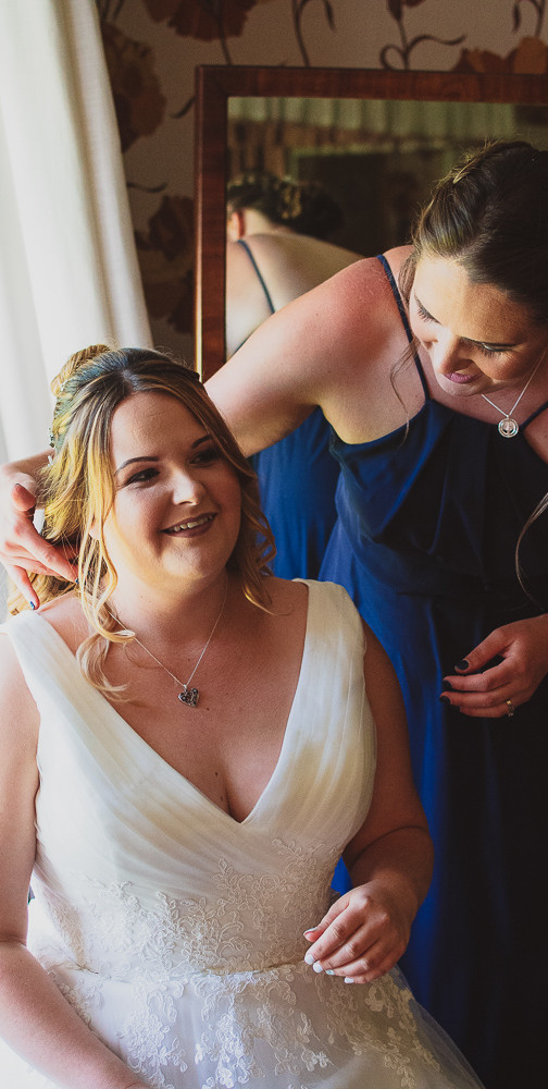Made of honour sorting out the bride's hair before she leaves for the ceremony