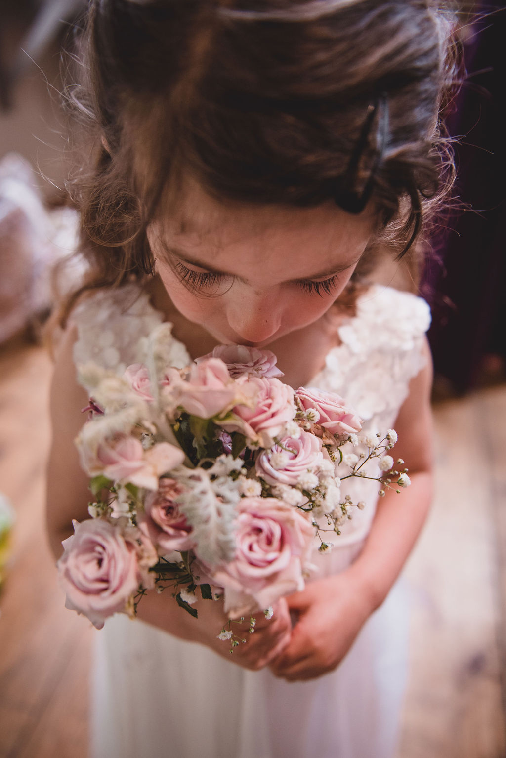 Flower girl smelling her bouquet at The Tythe Barn in Launton