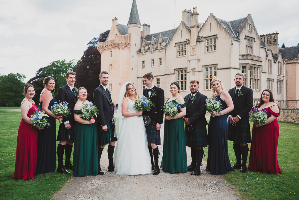 Bridal party with the bride and groom posing outside the castle wedding venue