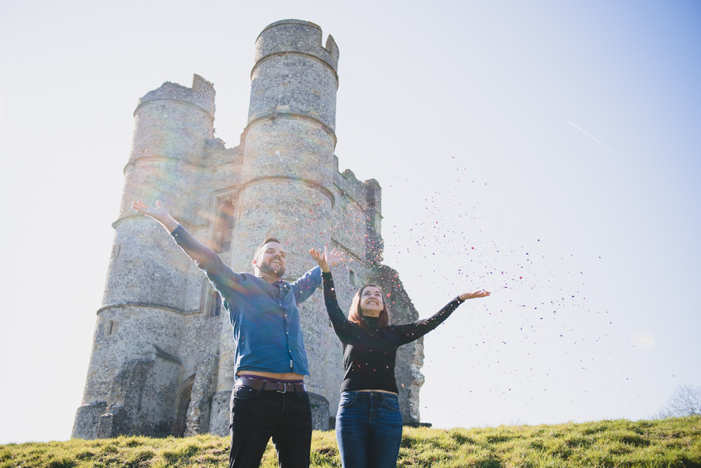 Couple throwing biodegradable confetti during their couple's photoshoot in front of an old castle.