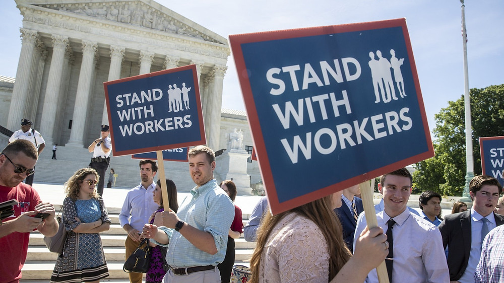 People gather Monday at the Supreme Court in Washington, D.C., awaiting a decision in an Illinois union dues case, Janus v. AFSCME. J. Scott Applewhite/AP