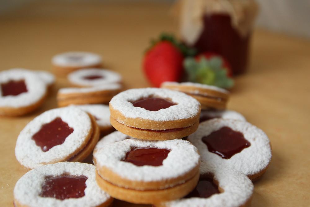 מערום של עוגיות ריבת תות על רקע ריבת תות בצנצנת ותותים טריים