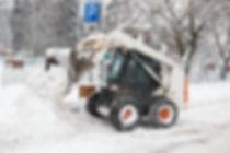 A bobcat removing snow