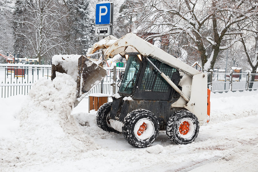 A bobcat skid steer removing snow