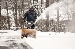 A worker operating a snow blower in the winter