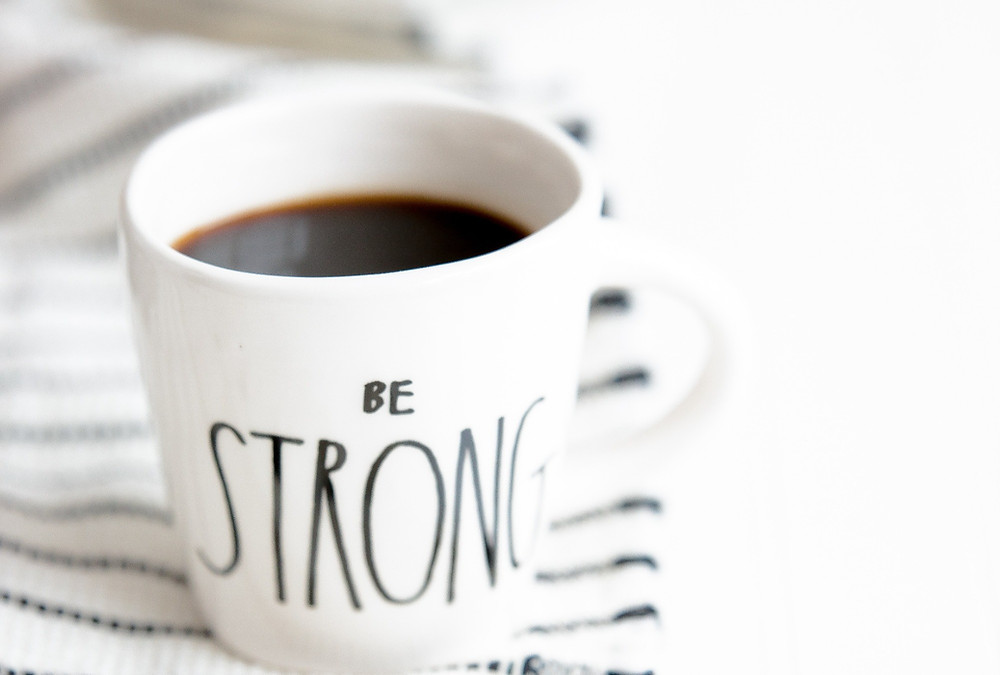 STRONG: Image showing a cup of black coffee that reads 'be strong'.