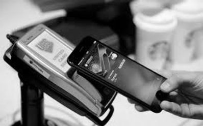 Background image of a mobile phone resting on a payment machine at a shop - showing how you can pay for products from mobile banking
