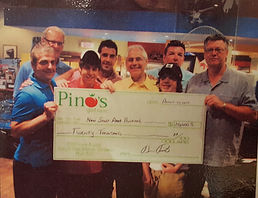 Pino's Get Fres staff holding up cheque for charity at supermarket