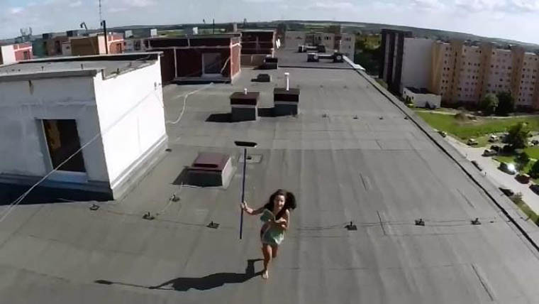 girl chasing drone with broom