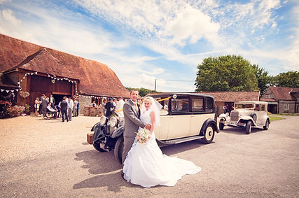 A newly marreid couple with vintage wedding cars