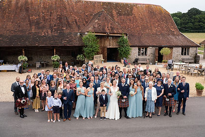 Wedding guests in a group photo outside Stockbridge Farm Barn