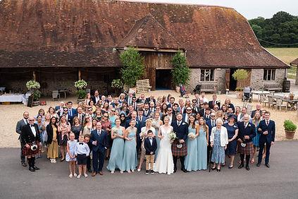 Wedding guests in a group photo outside Stockbridge Farm Barn