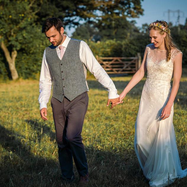 Newly married couple walking through the fields at Stockbridge Farm Barn