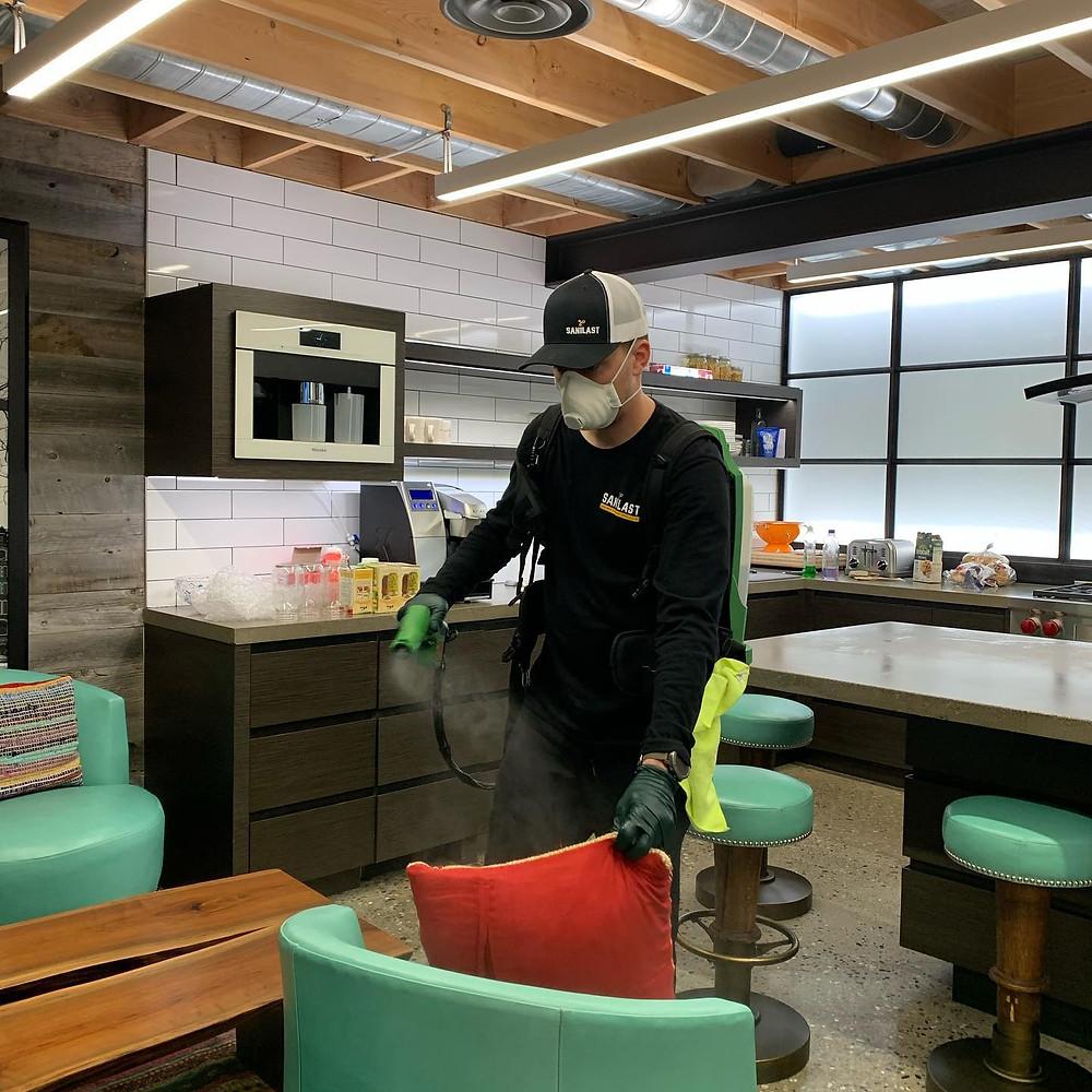Sanilast technician using an electrostatic sprayer to apply Zetrisil-based sanitizer in an office.