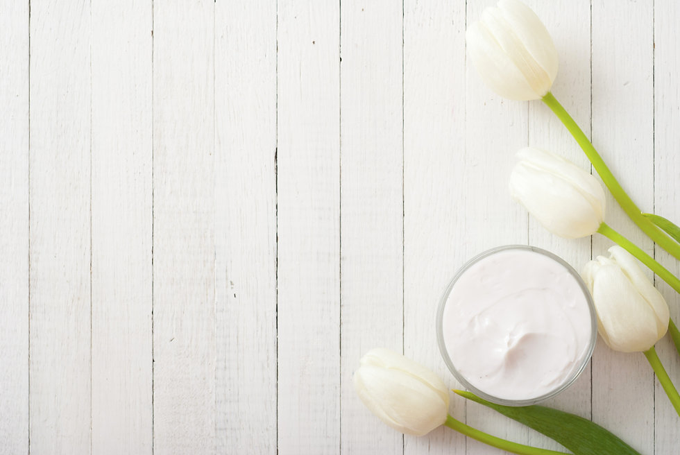 cosmetic cream with tulips on white wood
